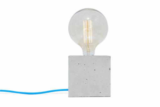 Een Qube tafellamp met een blauw snoer eraan bevestigd